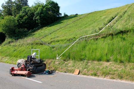 Le tracteur a dévalé une pente abrupte avant de s'écraser sur la route, blessant grièvement son conducteur.© Police cantonale jurassienne